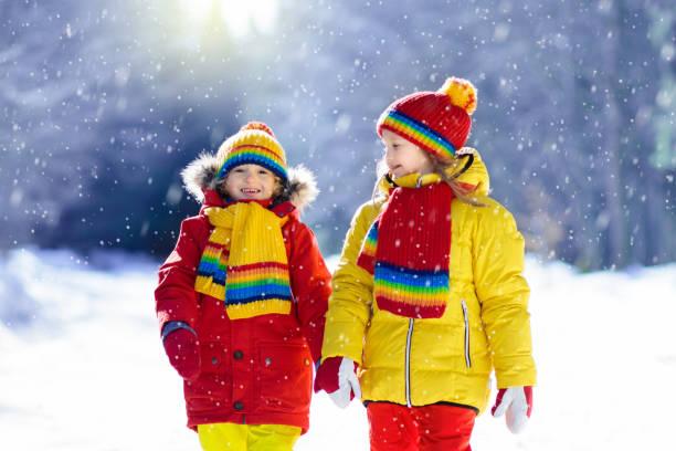孩子們冬天的雪球大戰。孩子們在雪地裡玩耍 - 冬天大衣 個照片及圖片檔