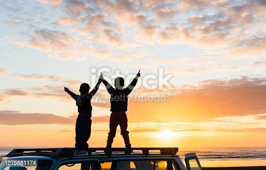 Kids at beach standing on the roof of 4wd and enjoying sunset.