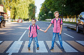 istock Kids with backpack walking, holding on warm day  on the road . 826237160