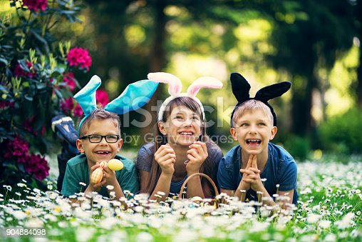 Three happy kids with bunny ears playing easter egg hunt in garden. Kids are lying in grass with