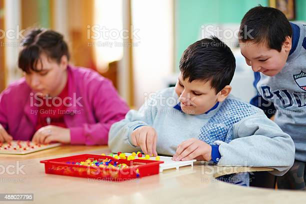 Kids with disabilities work at cognitive tasks picture id488027795?b=1&k=6&m=488027795&s=612x612&h=yq7mtfeabqyqncuy9t7l9rvvsxazhik1dq1cps1pxyc=