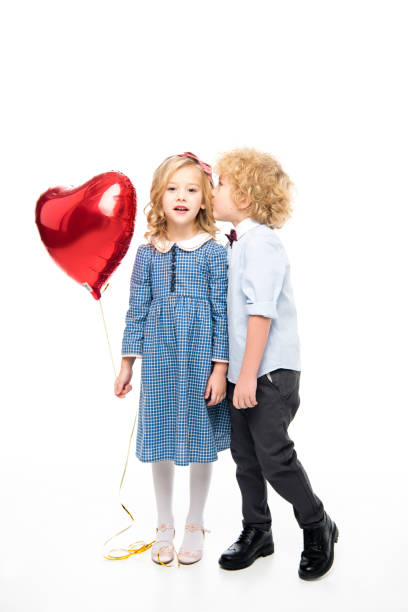 kids with heart shaped balloon - little girls little boys kissing love stock photos and pictures