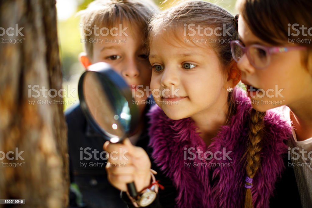 Kids with magnifying glass stock photo