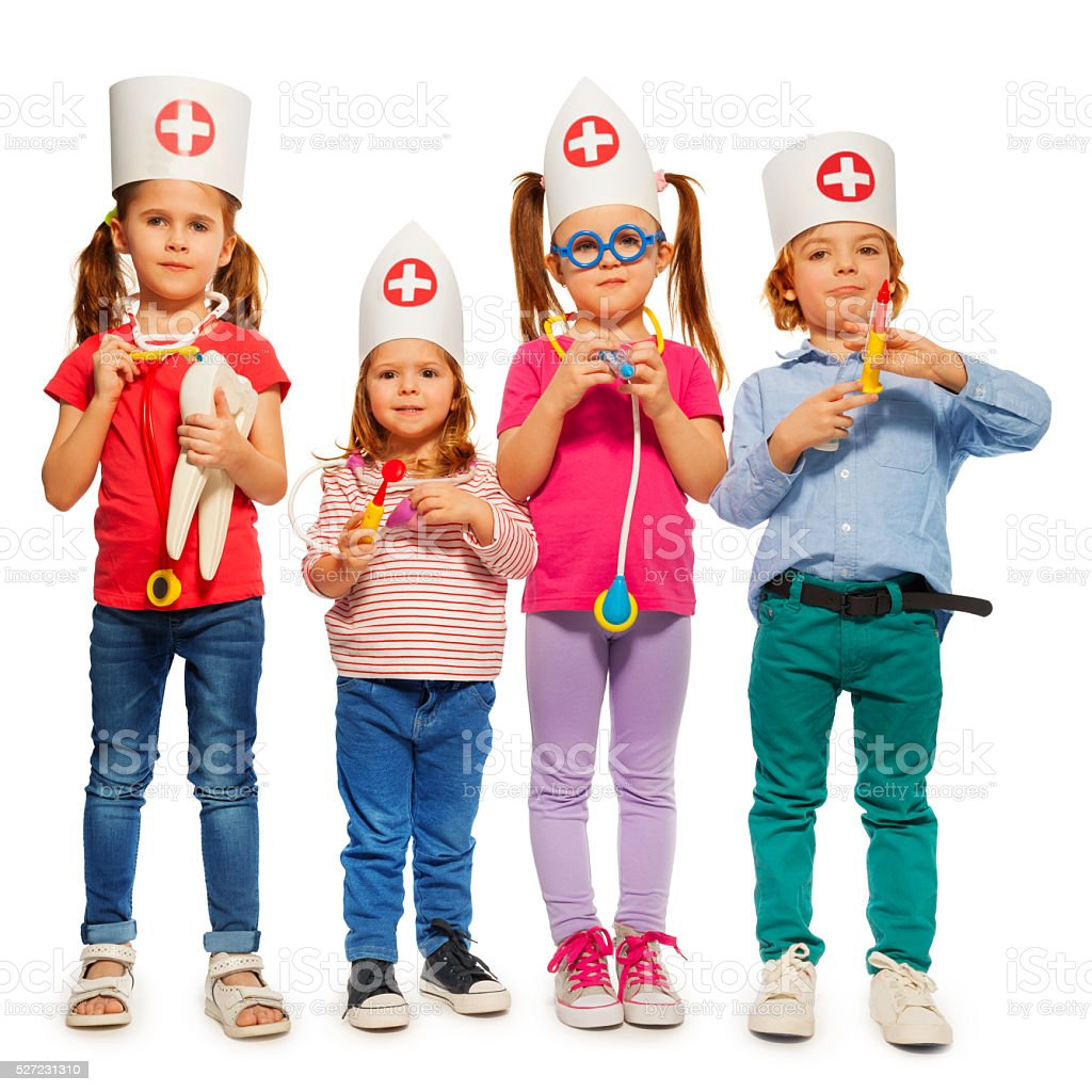 Kids with medical caps and toy doctor tools stock photo