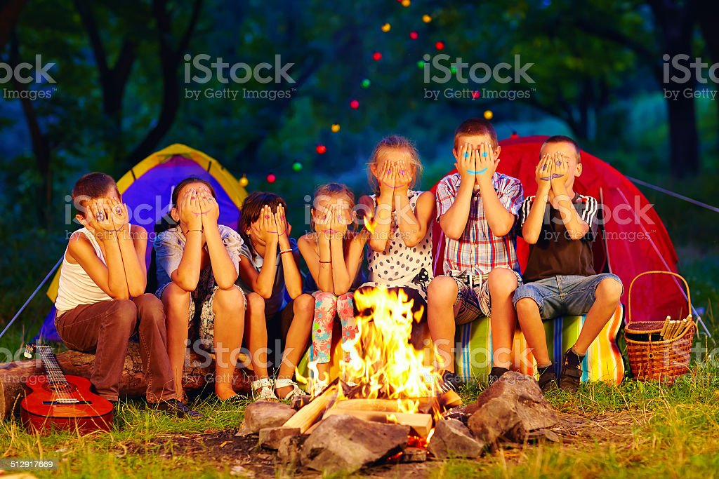 kids with painted faces on hands sitting around camp fire stock photo