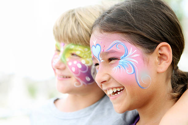 Kids with painted faces smiling stock photo