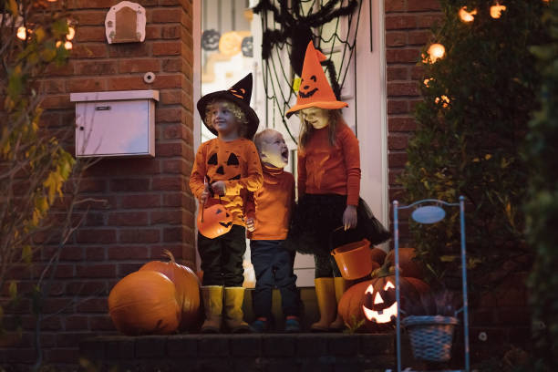 Kids with pumpkins in Halloween costumes Halloween trick or treat. Children in black and orange witch costume and hat standing at house door with pumpkin and spider decoration. Kids trick or treating. Boy and girl with candy buckets. magic trick stock pictures, royalty-free photos & images