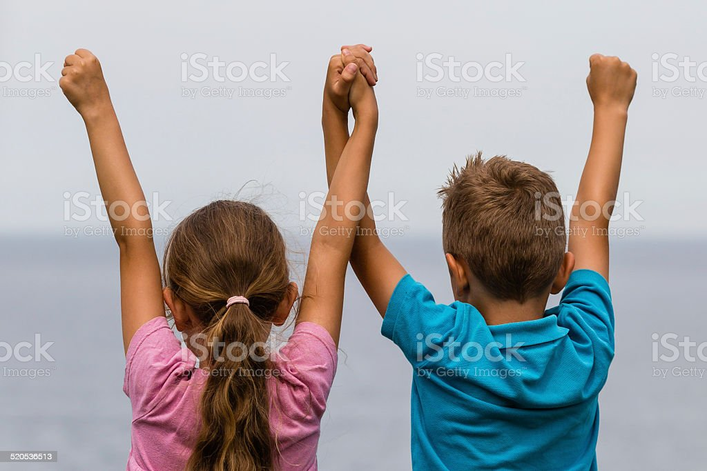 Kids with raised arms stock photo