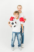 cute kids with soccer ball and boxing gloves smiling at camera isolated on white