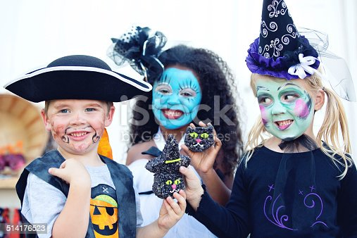 Three kindergarteners at a Halloween party holding up sweet treats for the camera. Pirate, witch and rag doll.