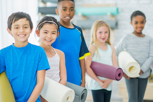 637804152 istock photo Kids With Yoga Mats 841582886