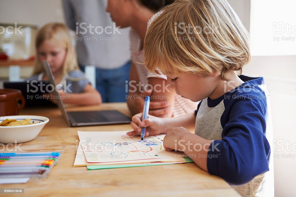 Kids working at kitchen table with their mother, close up stock photo