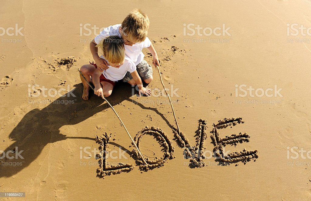 Kids writing in sand stock photo