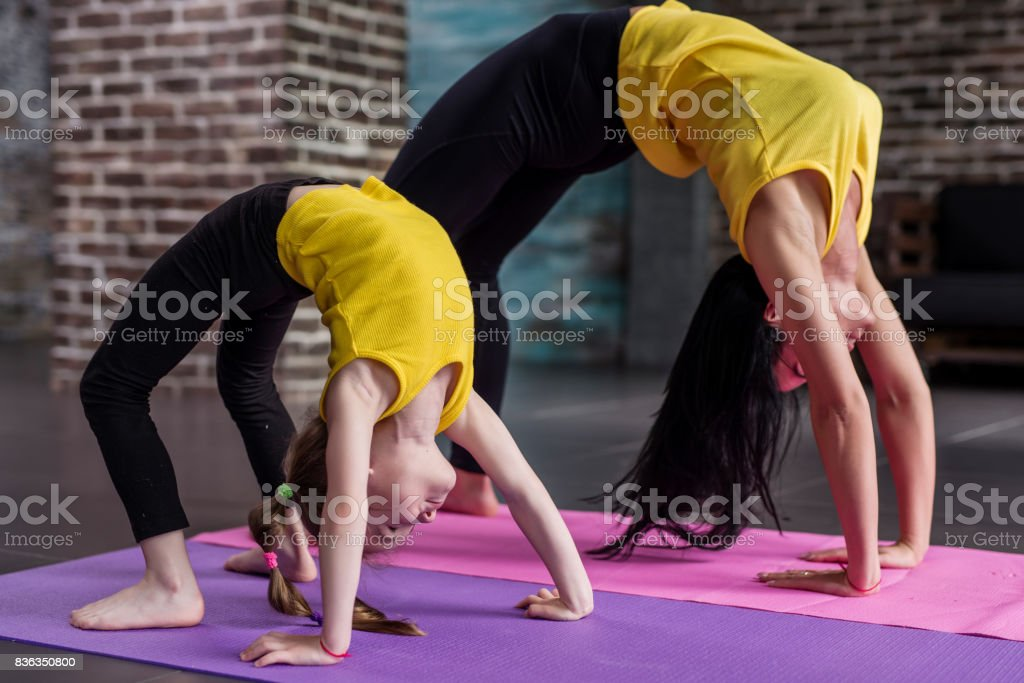 Kids yoga female teacher training a child girl standing in wheel pose working out in stylish sports studio stock photo