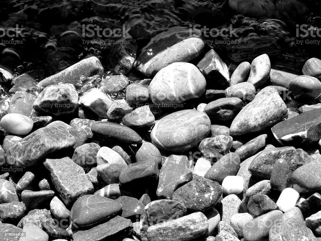 Kiesel am Seeufer in schwarz-weiß stock photo