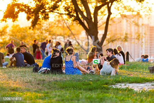 Kyiv, Ukraine - August 10, 2018: Landscape alley in Kiev capital city downtown during sunset golden sunlight with many people sitting having picnic