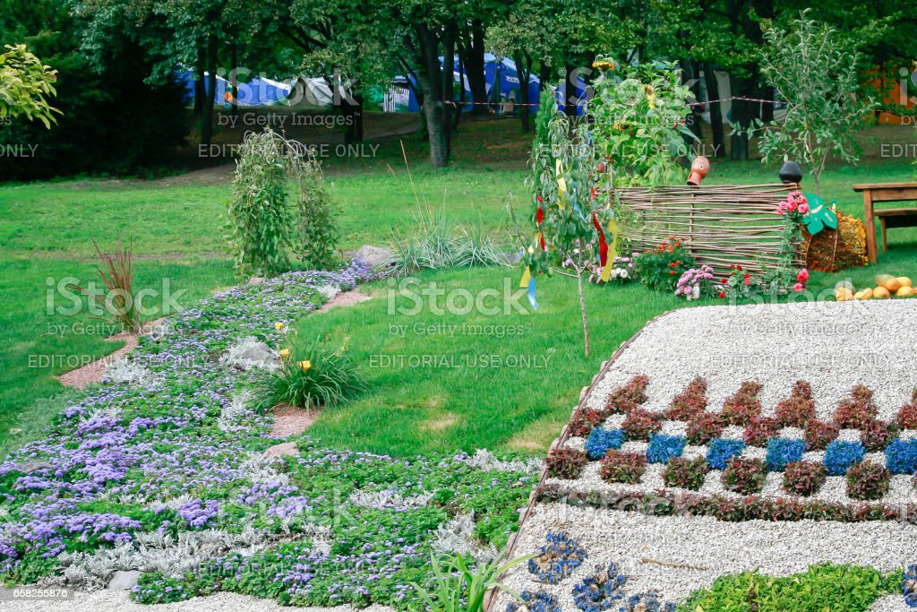Kiev. Ukraine-August 25,2010: Annual flower show at the Song Festival Grounds. Flower composition-bridge, river, mill. Visitors to view the exposition stock photo