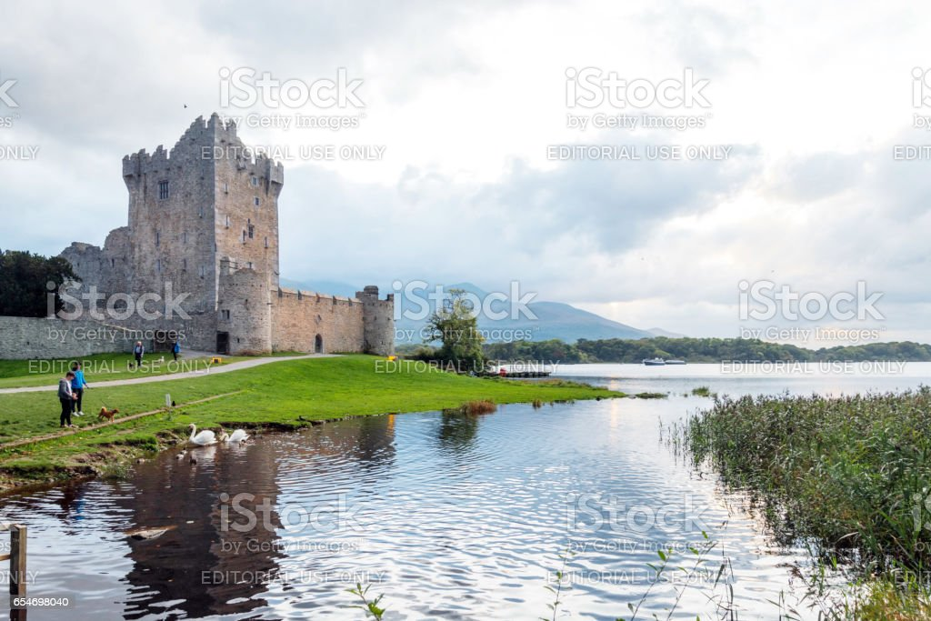 Killarney, Kerry, Ireland. October 5, 2016. Ross Castle on Lough Leane with two people on shore looking at two swans. Other people in the background walking around the grounds. stock photo