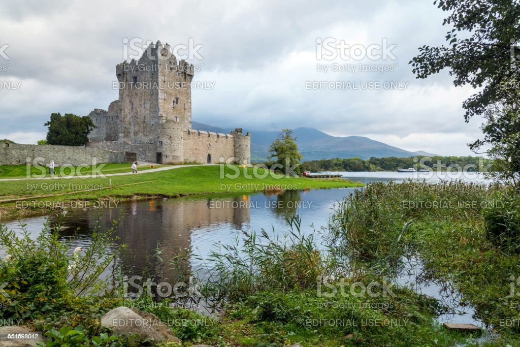 Killarny, Kerry, Ireland. October 5, 2016. Ross Castle on the on the Lough Leane with people walking around the grounds. Clouds overhead but no rain. The castle is reflected in the water. stock photo
