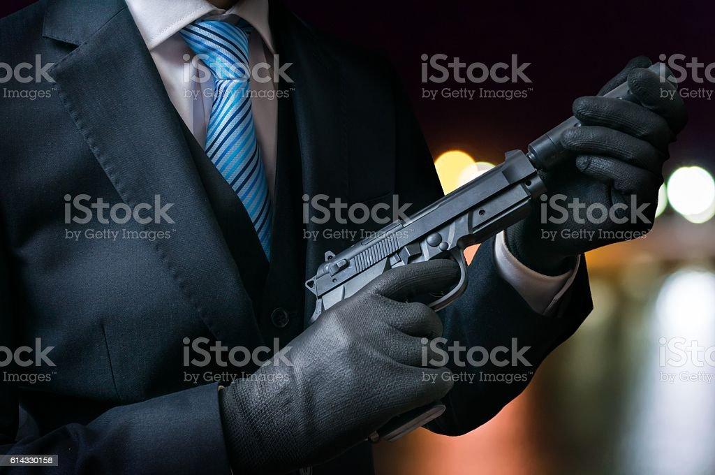 Killer holds gun with silencer in hands at night. - foto de acervo