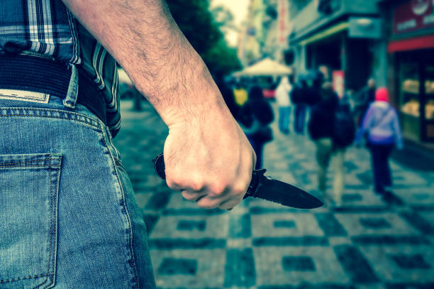 Killer is attacking with knife on crowd of people in public plac stock photo