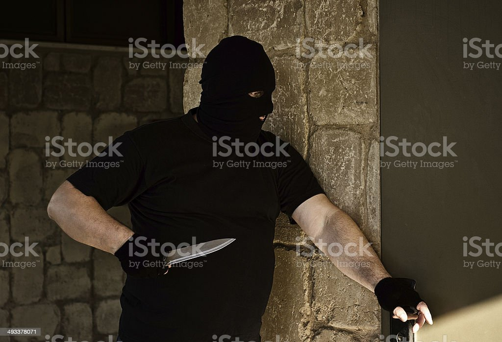 Killer is ready to break into the house stock photo