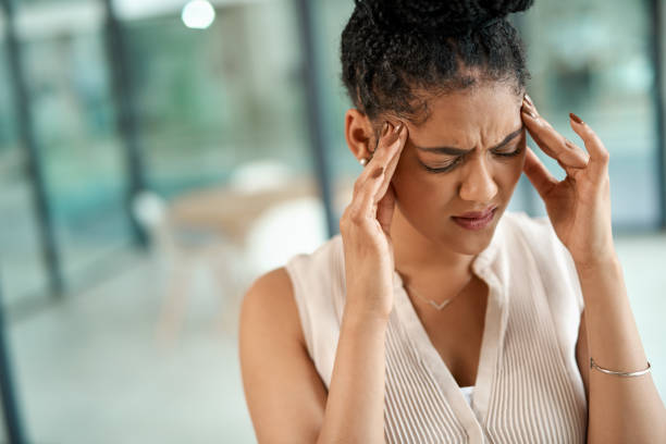 Killer migraine courtesy of major work stress Shot of a young businesswoman experiencing a stressful day at work headache stock pictures, royalty-free photos & images
