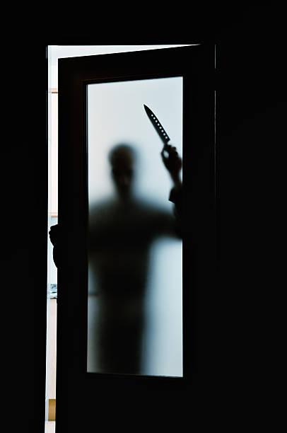 Killer silhueta atrás de portas de vidro fosco - foto de acervo