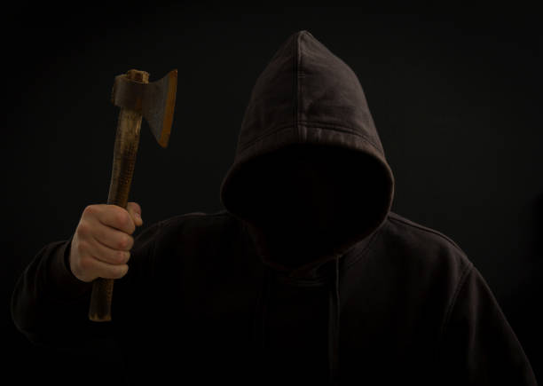A killer with a hatchet in his hand in the dark stock photo
