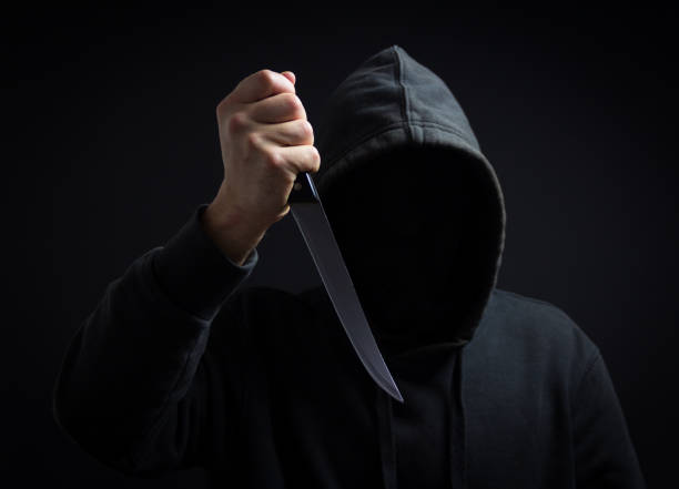 a killer with a knife in his hand in the dark - killer stock pictures, royalty-free photos & images