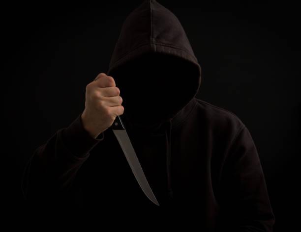 Um assassino com uma faca em sua mão no escuro - foto de acervo