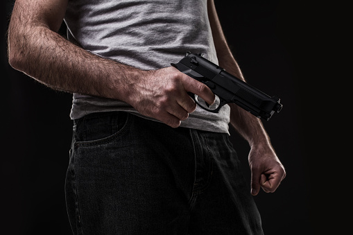 istock Killer with gun on black background at the studio 687511944