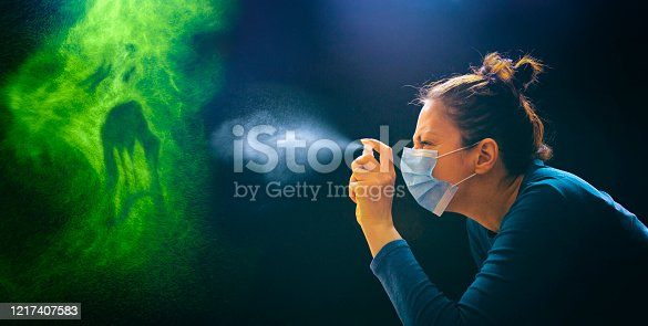 Masked woman spraying with antiseptic spray on green monster enemy coronavirus covid-19.