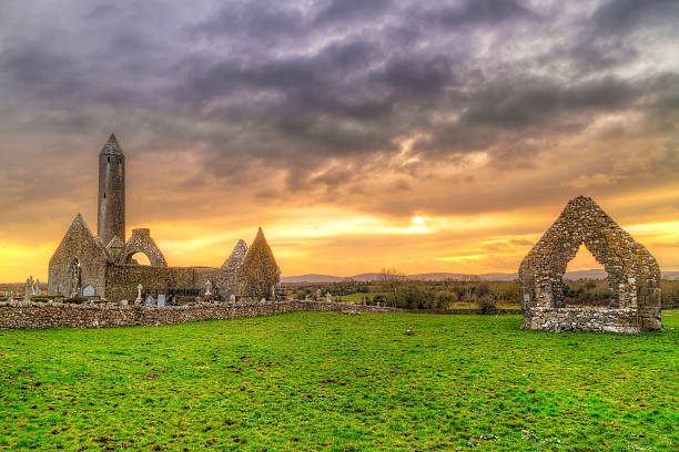 Kilmacduagh monastery with stone tower at sunset stock photo