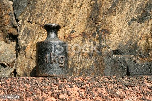 altes rostiges Gewicht aus Metall vor einer Steinmauer