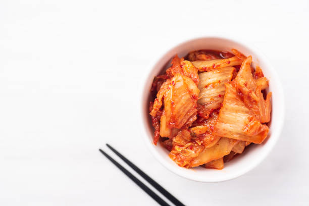 Kimchi cabbage in a bowl with chopsticks Kimchi cabbage in a bowl with chopsticks on white background, top view, Korean food kimchee stock pictures, royalty-free photos & images