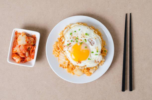 kimchi gebratener reis mit spiegelei obenauf - hausgemachter gebratener reis stock-fotos und bilder