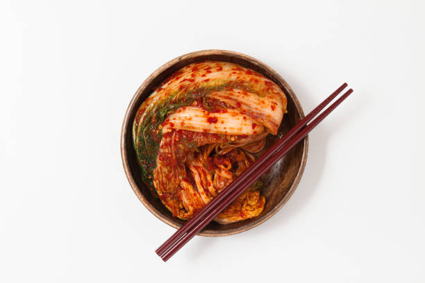Kimchi in wood dish isolated with chopsticks Kimchi in wood dish isolated with chopsticks kimchee stock pictures, royalty-free photos & images