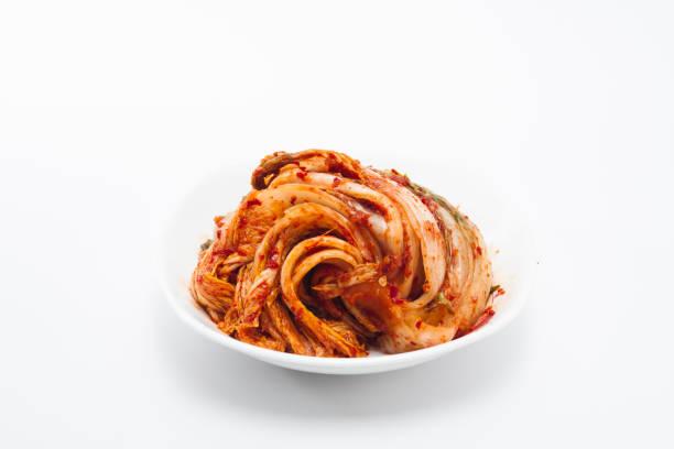 Kimchi on white dish isolated Kimchi on white dish isolated kimchee stock pictures, royalty-free photos & images