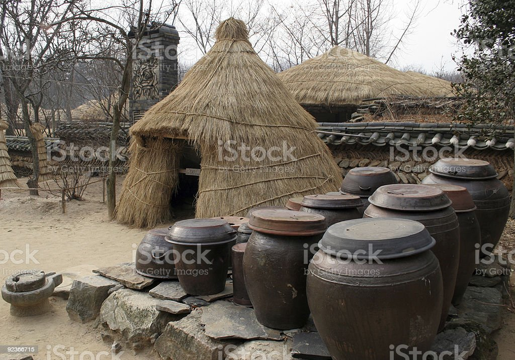 Kimchi (pickled cabbage) pots outside at straw tent royalty-free stock photo