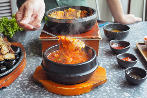Kimchi soup served in hot pot; traditional Korean food. Kimchi soup served in hot pot; traditional Korean food. Selective focus. kimchee stock pictures, royalty-free photos & images