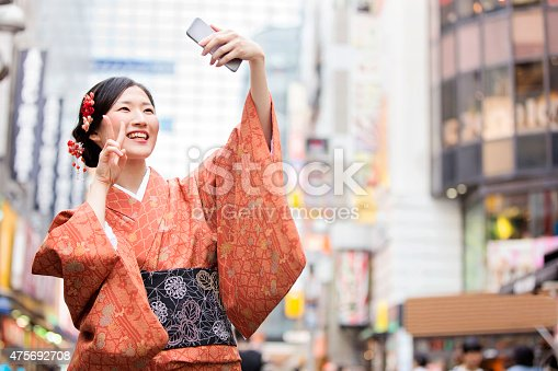 Japanese woman wearing a kimono takes a selfie in the city with her mobile phone.