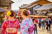 Kyoto, Japan - April 24, 2017: Japanese women wearing Japanese traditional kimono take selfie after visiting of Kiyomizu-dera Temple. Matsubara dori pedestrian shopping street on defocused background.