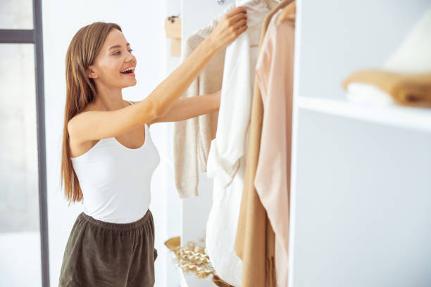 Kind brunette female looking at her shirt stock photo