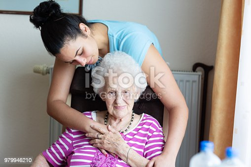 senior woman, 93 years old, wearing pink shirt, is embraced by young hispanic woman, who is standing behind her