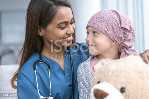 istock Kind doctor comforts girl with cancer 1141776211