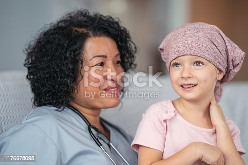 1041630080istockphoto Kind doctor comforts girl with cancer 1176678098