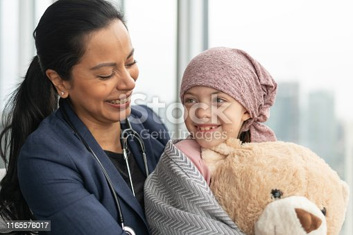 823893962 istock photo Kind doctor comforts young girl with cancer 1165576017
