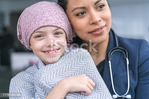 istock Kind doctor comforts young girl with cancer 1175130180