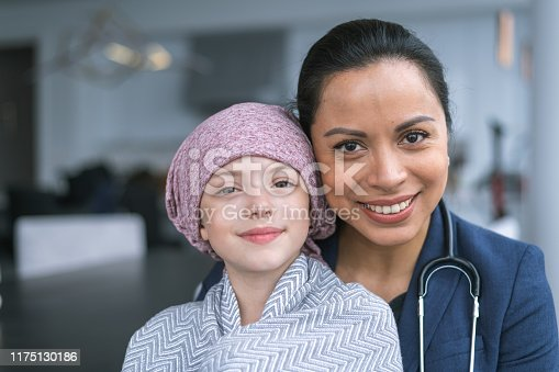 istock Kind doctor comforts young girl with cancer 1175130186